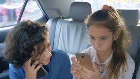 Ο αδελφός και η αδελφή διδύμων χρησιμοποιούν το τηλέφωνο διακινούμενη στο αυτοκίνητο στοκ εικόνες