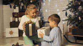 Ο αδελφός και η αδελφή τινάζουν τα κιβώτια με τα δώρα Χριστουγέννων κάτω από το χριστουγεννιάτικο δέντρο σε σε αργή κίνηση απόθεμα βίντεο