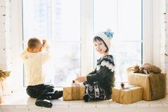 Ο αδελφός παιδιών και η αδελφή της προσχολικής ηλικίας κάθονται από το παράθυρο σε μια ηλιόλουστη ημέρα των Χριστουγέννων και παί Στοκ Φωτογραφία
