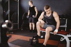 Ο αθλητής κάνει μια στάση οκλαδόν με ένα barbell στοκ εικόνα