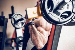 Ο αθλητής κάνει τις δελτοειδείς ασκήσεις στη μηχανή σφυριών στοκ φωτογραφίες με δικαίωμα ελεύθερης χρήσης
