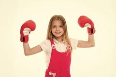 Ο αθλητής παιδιών παρουσιάζει δύναμη Ευτυχές παιδί στα εγκιβωτίζοντας γάντια που απομονώνεται στο λευκό Χαμόγελο μικρών κοριτσιών στοκ φωτογραφία
