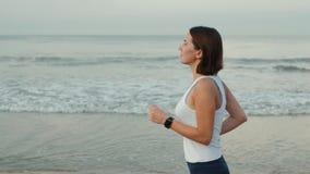 Ο αθλητικός θηλυκός δρομέας τρέχει τη φθορά smartwatch με την κενή μαύρη καμμμένη γυαλί οθόνη επαφής ζωνών ρολογιών στη φυσική ωκ απόθεμα βίντεο