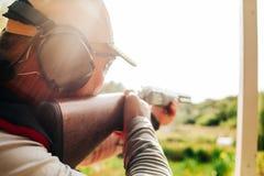 Ο αθλητικός τύπος ελεύθερων σκοπευτών πυροβολεί τους πετώντας στόχους κυνηγετικών όπλων έξω στοκ φωτογραφίες
