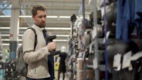 Ο αθλητικός τύπος επιλέγει έναν αλτήρα για τον σε ένα κατάστημα, που δοκιμάζει το βάρος φιλμ μικρού μήκους