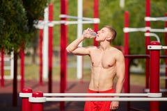 Ο αθλητικός τύπος πίνει το νερό πρίν ασκεί σε μια περιοχή κατάρτισης στην οδό στοκ εικόνες