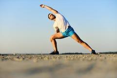 Ο αθλητικός τύπος φορά την άσπρη μπλούζα και τα μπλε σορτς τεντώνοντας τους μυς του στοκ εικόνες με δικαίωμα ελεύθερης χρήσης