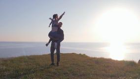 Ο αθλητισμός υπαίθρια, γυναίκα αθλητών πηδά στον άνδρα και τις περιστροφές στον πράσινο χορτοτάπητα στην παραλία στη φωτεινή ηλιο φιλμ μικρού μήκους