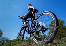 Ο αθλητής κοριτσιών στη μαύρη φόρμα γυμναστικής οδηγά ένα ποδήλατο το πρωί στο πάρκο Στοκ φωτογραφία με δικαίωμα ελεύθερης χρήσης