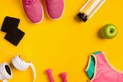 Ο αθλητής ` s έθεσε με το θηλυκούς ιματισμό, τους αλτήρες και το μπουκάλι νερό στο κίτρινο υπόβαθρο Στοκ φωτογραφίες με δικαίωμα ελεύθερης χρήσης
