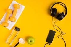 Ο αθλητής ` s έθεσε με το θηλυκούς ιματισμό, τους αλτήρες και το μπουκάλι νερό στο κίτρινο υπόβαθρο Στοκ εικόνα με δικαίωμα ελεύθερης χρήσης