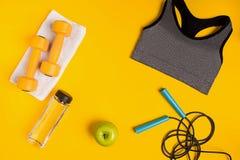 Ο αθλητής ` s έθεσε με το θηλυκούς ιματισμό, τους αλτήρες και το μπουκάλι νερό στο κίτρινο υπόβαθρο Στοκ εικόνες με δικαίωμα ελεύθερης χρήσης