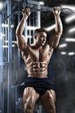 Ο αθλητικός μυϊκός τύπος προετοιμάζεται να κάνει τις ασκήσεις με τον αθλητικό εκπαιδευτή σε μια γυμναστική Στοκ Φωτογραφίες