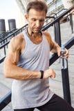 Ο αθλητικός τύπος με το μπουκάλι νερό στηρίζεται και ελέγχει το έξυπνο ρολόι του μετά από να τρέξει ικανότητα, αθλητισμός, στοκ φωτογραφία