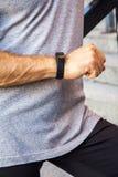 Ο αθλητικός τύπος με το μπουκάλι νερό στηρίζεται και ελέγχει το έξυπνο ρολόι του μετά από να τρέξει στοκ εικόνα