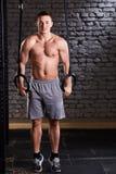 Ο αθλητικός τύπος που κάνει το τράβηγμα UPS με τα γυμναστικά δαχτυλίδια για τη δύναμη και crossfit ασκεί ενάντια στο τουβλότοιχο Στοκ Φωτογραφία