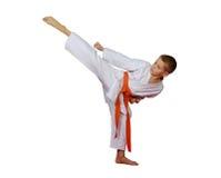 Ο αθλητικός τύπος σε ένα κιμονό κτύπησε ένα κυκλικό υψηλό πόδι λακτίσματος Στοκ Φωτογραφία