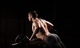 ο αθλητικός τύπος δύναμης, εκτελεί την άσκηση με τους αλτήρες Στοκ Φωτογραφίες