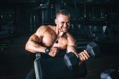 Ο αθλητικός τύπος δύναμης bodybuilder, εκτελεί την άσκηση με τους αλτήρες, στη σκοτεινή γυμναστική Στοκ Εικόνες