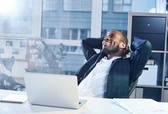 Ο αισιόδοξος χαριτωμένος διευθυντής κάθεται στο γραφείο Στοκ Εικόνες