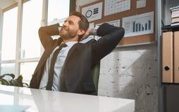 Ο αισιόδοξος χαριτωμένος διευθυντής κάθεται στο γραφείο Στοκ Εικόνα