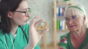 Ο ακουομέτρης γιατρών λέει σε μια ηλικιωμένη γυναίκα για την ενίσχυση ακρόασης φιλμ μικρού μήκους