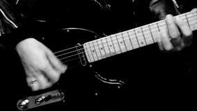 ο ακουστικός κιθαρίστας κιθάρων λεπτομερειών δίνει το instrumant μουσικό παιχνίδι φορέων εκτελεστών φιλμ μικρού μήκους