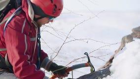 Ο ακραίος τουρίστας σπάζει το ανθεκτικό χιόνι με μια επιλογή πάγου ρωγμών φορά ένα κόκκινες ειδικές κοστούμι, ένα σακίδιο πλάτης  απόθεμα βίντεο