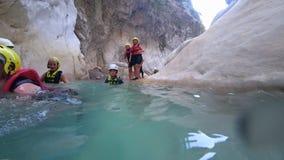 Ο ακραίος τουρισμός, επιχείρηση των τουριστών με τα παιδιά στα ενεργά Σαββατοκύριακα στα ειδικά κοστούμια κολυμπά στη σπηλιά νερο απόθεμα βίντεο