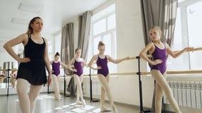 Ο ακριβής δάσκαλος μπαλέτου καταδεικνύει τα πόδια και οπλίζει τις θέσεις ενώ τα επιμελή μικρά κορίτσια επαναλαμβάνουν μετά από τη απόθεμα βίντεο