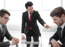 Ο ακριβής προϊστάμενος επιπλήττει το μη επαγγελματικό υπάλληλο σε μια εργαζόμενη συνεδρίαση στοκ εικόνα