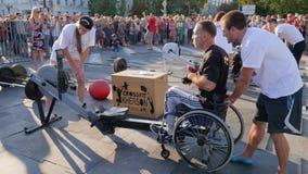 Ο ακρωτηριασμένος τύπος στην αναπηρική καρέκλα τραβά το καλώδιο στον αθλητισμό εκπαιδευτικός τις συσκευές με τους εκπαιδευτές στο απόθεμα βίντεο