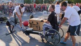 Ο ακρωτηριασμένος τύπος στην αναπηρική καρέκλα τραβά το καλώδιο στον αθλητισμό εκπαιδευτικός τις συσκευές με τους εκπαιδευτές στο φιλμ μικρού μήκους