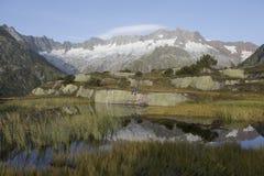 Ο αλπινιστής κάνει ένα σπάσιμο κατά τη διάρκεια μιας ανατολής σε μια λίμνη βουνών στα όρη Στοκ φωτογραφίες με δικαίωμα ελεύθερης χρήσης