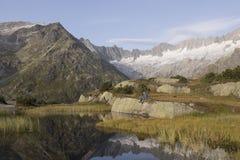 Ο αλπινιστής κάνει ένα σπάσιμο κατά τη διάρκεια μιας ανατολής σε μια λίμνη βουνών στα όρη Στοκ Φωτογραφίες