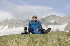 Ο αλπινιστής κάνει ένα σπάσιμο τσαγιού πριν από τις συναρπαστικές θέες βουνού Στοκ εικόνες με δικαίωμα ελεύθερης χρήσης