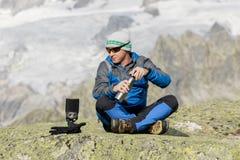 Ο αλπινιστής κάνει ένα σπάσιμο τσαγιού πριν από τις συναρπαστικές θέες βουνού Στοκ φωτογραφία με δικαίωμα ελεύθερης χρήσης
