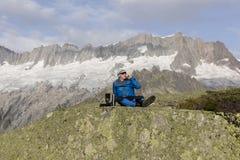 Ο αλπινιστής κάνει ένα σπάσιμο τσαγιού πριν από τις συναρπαστικές θέες βουνού Στοκ Εικόνες