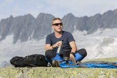 Ο αλπινιστής προετοιμάζει ένα τσάι κατά τη διάρκεια ενός σπασίματος Στοκ Εικόνα