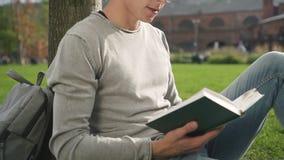 Ο αμερικανικός ευφυής τύπος κάθεται στο δέντρο κοντά στο κολλέγιο απόθεμα βίντεο