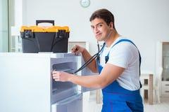 Ο ανάδοχος επισκευαστών που επισκευάζει το ψυγείο στη diy έννοια Στοκ Φωτογραφία