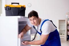 Ο ανάδοχος επισκευαστών που επισκευάζει το ψυγείο στη diy έννοια Στοκ Εικόνες
