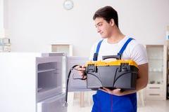 Ο ανάδοχος επισκευαστών που επισκευάζει το ψυγείο στη diy έννοια Στοκ Εικόνα