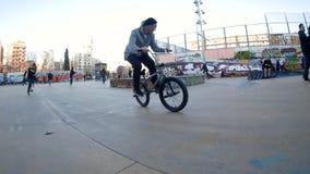 Ο αναβάτης ατόμων BMX κάνει τις διαφορετικά ακροβατικές επιδείξεις και τα τεχνάσματα στο ποδήλατο στο αστικό περιβάλλον απόθεμα βίντεο