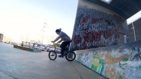 Ο αναβάτης ατόμων BMX κάνει τις διαφορετικά περιστροφές και τα τεχνάσματα στο ποδήλατο στο αστικό περιβάλλον απόθεμα βίντεο