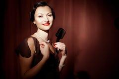 Ο αναδρομικός τραγουδιστής τραγουδά στην εκμετάλλευση το εκλεκτής ποιότητας μικρόφωνο στοκ εικόνα