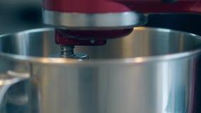 Ο αναμίκτης περιστρέφει βαθμιαία στο μεγάλο κύπελλο μετάλλων για να προετοιμάσει την κρέμα απόθεμα βίντεο