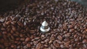 Ο αναμίκτης της συσκευής των ψήνοντας αρωματικών φασολιών καφέ κοντά επάνω σε σε αργή κίνηση Στάδια της προετοιμασίας καφέ και φιλμ μικρού μήκους