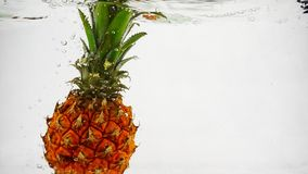 Ο ανανάς βυθίζει αργά στο νερό με τα κύματα και τις φυσαλίδες φιλμ μικρού μήκους