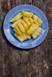 Ο ανανάς που κόβεται στα κομμάτια, τους τακτοποιεί σε ένα μπλε πιάτο Στοκ Εικόνες